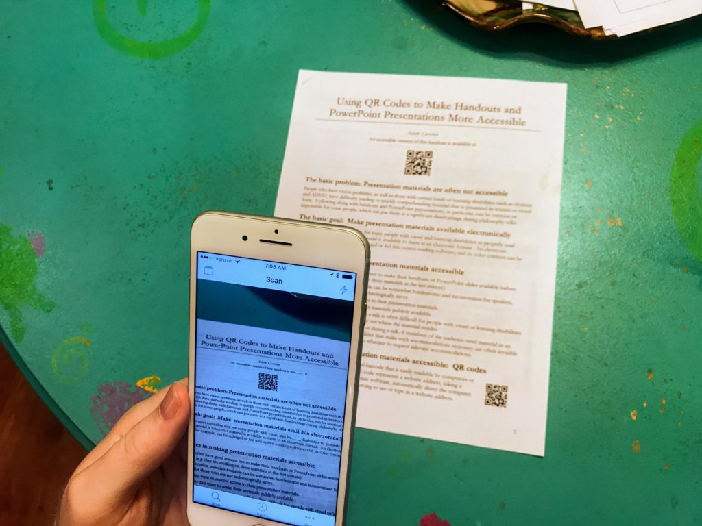 Shows an Apple iPhone pointed at a document with a QR code on it. The phone has a QR code reader app open and shows an image of the document with the QR code in the middle.