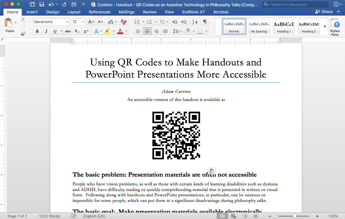 Shows a Mac computer, after the QR code has been pasted into a Word document, near the top.
